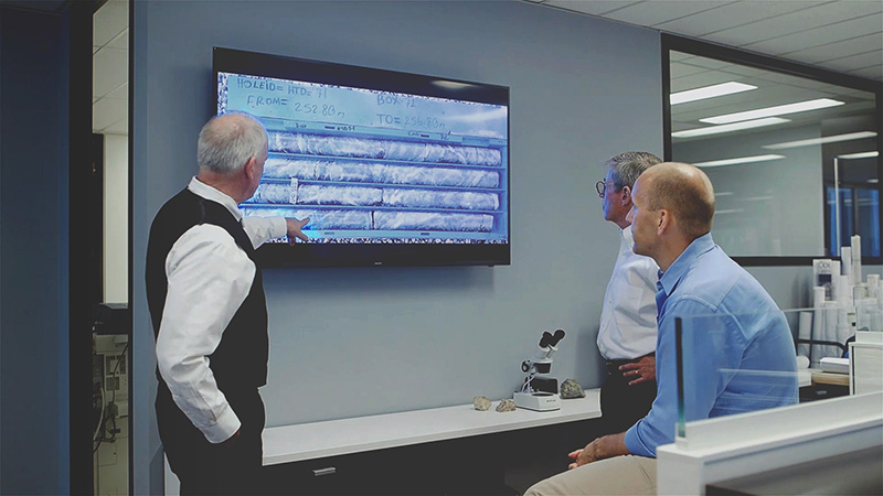 Team looking at ore samples on a screen